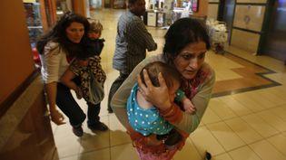 """Une femme porte son enfant dans le centre commercial""""Westgate Mall"""", situé à Nairobi (Kenya), et cible d'une attaque terroriste le 21 septembre 2013. (GORAN TOMASEVIC / REUTERS)"""