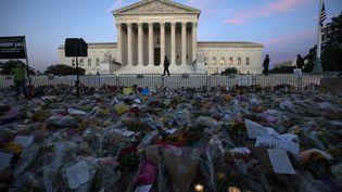 Des fleurs et des bougiessont déposées devant la Cour suprême pour honorer la mémoire de la juge Ruth Bader Ginsburg, à Washington, le 19 septembre 2020. (JOSE LUIS MAGANA / AFP)
