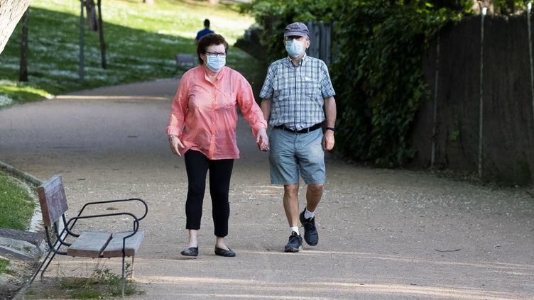 Un couple se promène dans un parc, à Madrid (Espagne), samedi 2 mai 2020. (OSCAR GONZALEZ / NURPHOTO / AFP)