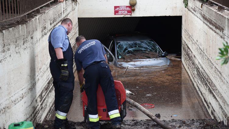 Lundi 5 octobre, des personnes pompent l'eau boueuse dans le parking sous-terrain d'une résidence où quatre personnes ont trouvé la mort, à Mandelieu-La-Napoule (Alpes-Maritimes). (ANNE-CHRISTINE POUJOULAT / AFP)