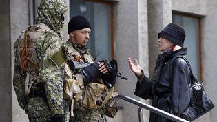 Une habitante discute avec des forces armées pro-russes devant la mairie de Sloviansk (Ukraine), le 14 avril 2014. (GLEB GARANICH / REUTERS)