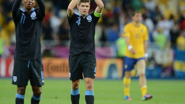 Le milieu de terrain Steven Gerrard et l'attaquant Ashley Young célèbrent la victoire de l'Angleterre (3-2) contre la Suède, le 15 juin 2012 à Kiev en Ukraine. (JEFF PACHOUD / AFP)