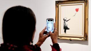 """L'oeuvre Girl with balloon de l'artiste anglais Banksy, lors de l'exposition """"Guerre, capitalisme et liberté"""" au Palazzo Cipolla, à Rome (Italie) le 23 mai 2016. (VINCENZO PINTO / AFP)"""
