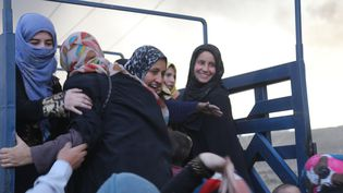 Des femmes sourient à leur arrivée àQayyarah, après avoir fui lenord de l'Irak. (FERIQ FEREC / ANADOLU AGENCY)