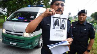 Des policiers malaisiens montrent un avis de recherche concernant Nora Quoirin, le 9 avril 2019 à Seremban. (MOHD RASFAN / AFP)