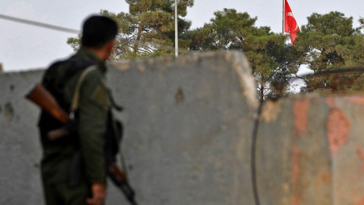 Un combattant kurde observe un drapeau turc de l'autre côté de la frontière, depuis la ville de Kobané, en octobre 2019 (AFP)