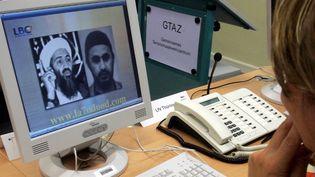 Une employée d'un centre d'opérations anti-terrorisme regarde une photo d'Oussama Ben Laden et une d'Abou Moussab al-Zarqaoui, en août 2005 à Berlin (Allemagne). (MARCUS BRANDT / DDP)