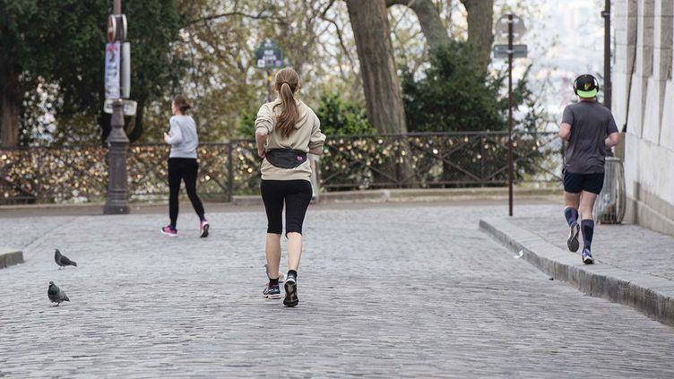 Des joggeurs dans Paris, le 19 mars 2020. (HUGO PASSARELLO LUNA / HANS LUCAS)