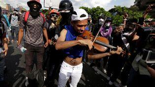 Un violoniste participe à une manifestation contre le président vénézuélien Nicolas Maduro, à Caracas, le 6 mai 2017. (MARCO BELLO / REUTERS)
