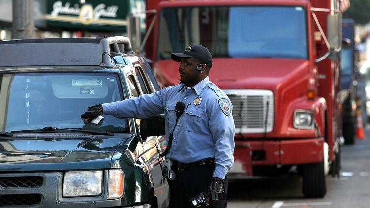 Un agent de la ville de San Francisco (Californie) met une contravention pour mauvais stationnement, le 21 janvier 2011. (JUSTIN SULLIVAN / AFP)