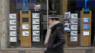 Un homme passe devant une agence immobilière, le 18 mars 2013, à Paris. (FRED DUFOUR / AFP)