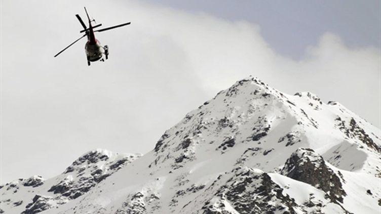 Un hélicoptère de recherches au dessus du village suisse de Bourg-Saint-Pierre, après une avalanche, le 23 mars 2011 (AFP/FABRICE COFFRINI)