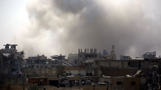De la fumée s'élève du quartier al-Sanaa de Raqqa (Syrie), près de la vieille ville, alors que les Forces démocratiques syriennes combattent l'Etat islamique, le 13 août 2017. (DELIL SOULEIMAN / AFP)