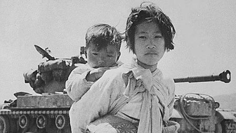 1951 en Corée. Une jeune Coréenne portant son frère. Derrière eux, un char américain. (AFP/national archives)