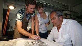 """L'égyptologue italien Francesco Tiradritti (à droite), la responsable de la restauration et de la conservation des ouvrages de la bibliothèque d'Ajaccio, Vannina Schirinski-Schikhmatoff (au centre) et le conservateur italien Simone Martini observent une planche du """"Thesaurus Hyeroglyphicorum""""  (PASCAL POCHARD-CASABIANCA / AFP)"""