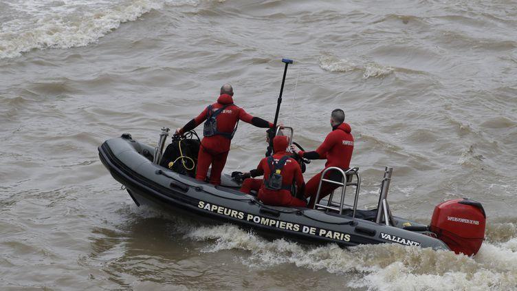 Des pompiers recherchent le corps de la jeune policière noyée dans la Seine lors d'un exercice, le 5 janvier 2018 à Paris. (THOMAS SAMSON / AFP)