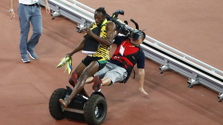 Alors qu'il célèbre son nouveau titre de champion du monde du 200 m, jeudi 27 août à Pékin,le Jamaïcain Usain Bolt est renversé par un caméraman qui le filmait en circulant sur un gyropode Segway en bord de piste. (ROLEX DELA PENA / EPA)