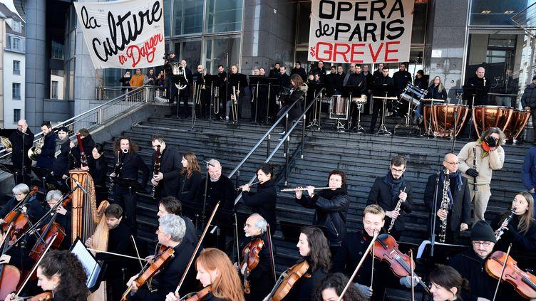 Des musiciens grévistes de l'Opéra Bastille jouent devant l'institution parisienne le 31 décembre 2019 en signe de protestation contre la réforme des retraites. (JULIEN MATTIA / ANADOLU AGENCY / AFP)