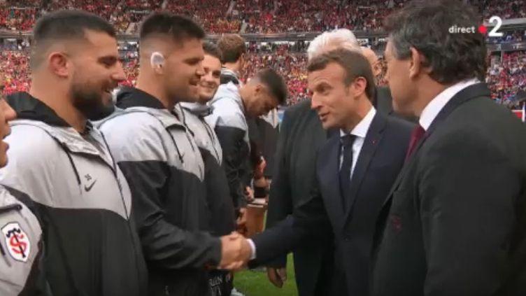 Emmanuel Macron salue le joueur du Stade toulousainMaks Van Dyk, le 15 juin 2016, lors de la finale du Top 14, au tade de France, à Saint-Denis. (FRANCE 2 / FRANCEINFO)