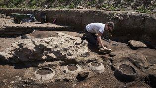 Une archéologue effectue des fouilles sur un site de Sainte-Colombe (Rône), le 31 juillet 2017. (JEAN-PHILIPPE KSIAZEK / AFP)