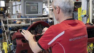 Un employé de l'usine Porsche de Stuttgart, le 21 février 2019 (THOMAS KIENZLE / AFP)