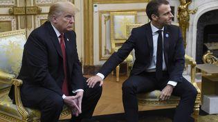 Emmanuel Macron pose une main sur un genou de Donald Trump, le 10 novembre 2018, à l'Elysée, à Paris. (SAUL LOEB / AFP)