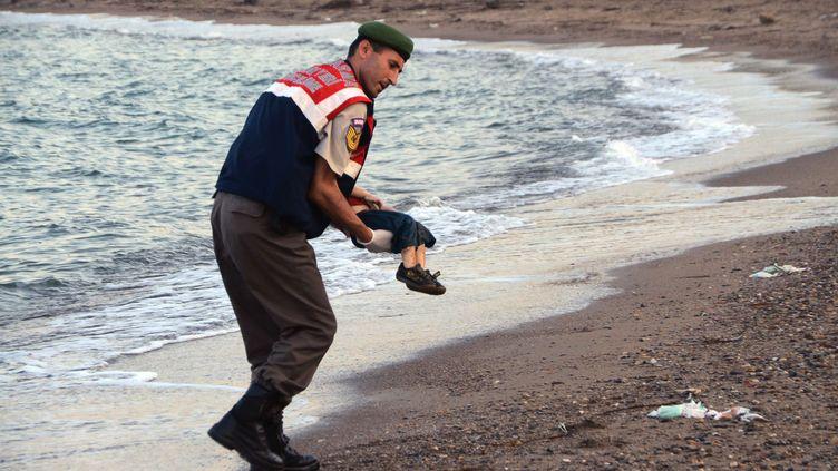 Un officier turc évacue le corps d'un jeune migrant mort, le 2 septembre 2015 à Bodrum (Turquie). (SIPA / AP)