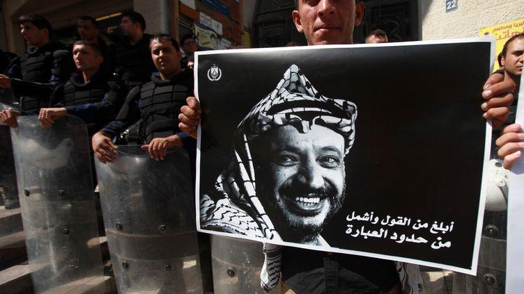 Un Palestinien brandit un portrait de Yasser Arafat, lors d'une manifestation à Ramallah, en Cisjordanie, le 15 septembre 2013. (ABBAS MOMANI / AFP)
