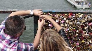 Un couple accroche un cadenas d'amour sur le Pont des Arts à Paris. Un geste impossible à partir du 1er juin 2015.  (Charly Triballeau / AFP)