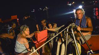 Des habitants du village de Mati (Grèce) évacués le 23 juillet 2018 après les incendies. (ANGELOS TZORTZINIS / AFP)