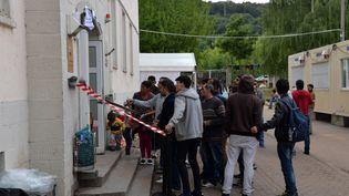 Des réfugiés attendent le 18 août 2015 devant un centre d'accueil de Trèves, en Allemagne. (HARALD TITTEL / DPA/AFP)