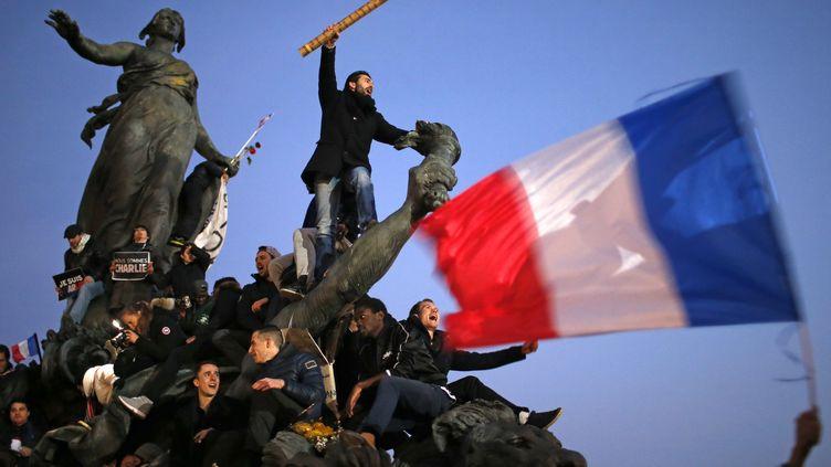 """Après la dispersion du cortège, de nombreux participants sont restés sur différentes places parisiennes, comme ici, place de la Nation, où a été prise cette photo vite baptisée """"Le crayon guidant le peuple"""" sur les réseaux sociaux, le 11 janvier 2015. ( STEPHANE MAHE / REUTERS)"""