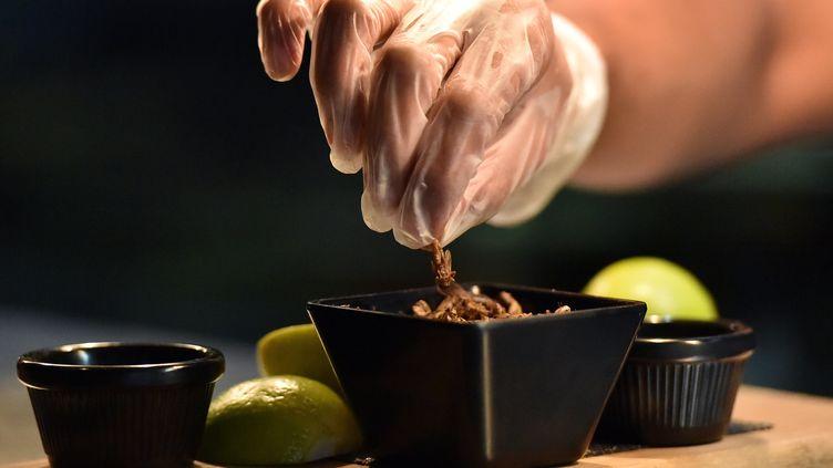 Cette photo prise le 16 mars 2017 montre le sous-chef Nowshad Alam Rasel donnant la touche finale à son plat de cricket emblématique dans un restaurant de Sydney. - Il est maintenant possible d'essayer d'acheter des cafards rôtis, des fourmis au miel, du ver de farine et du maïs soufflé au chocolat. Bien que la cuisine reste une nouveauté, sa popularité ne cesse de croître. (SAEED KHAN / AFP)