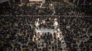 Un premier sit-in à l'aéroport d'Hong Kong pour dénoncer les violences policières, le 12 août 2019, force les autorités à suspendre l'activité de l'aéroport. (VERNON YUEN / NURPHOTO / AFP)