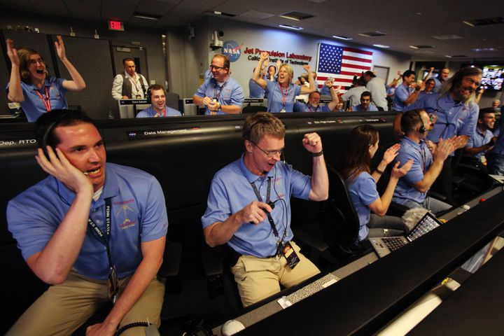 Des ingénieurs de la mission Mars Curiosity fêtent l'amarssisage réussi de leur robot, le 5 août 2012 à Pasadena (Californie). (BRIAN VAN DER BRUG / AFP)