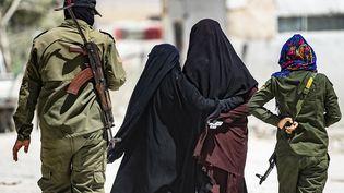 Deux femmes ayant appartenu au groupe terroriste Etat islamique sont escortées par une patrouille dans le camp d'al-Hol, dans le nord-est de la Syrie, le 23 juillet 2019. (DELIL SOULEIMAN / AFP)