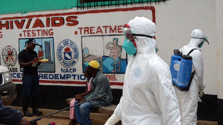 Des membres de la Croix rouge s'occupent du corps d'une victime d'Ebola, le 12 septembre 2014 au Liberia. (ZOOM DOSSO / AFP)