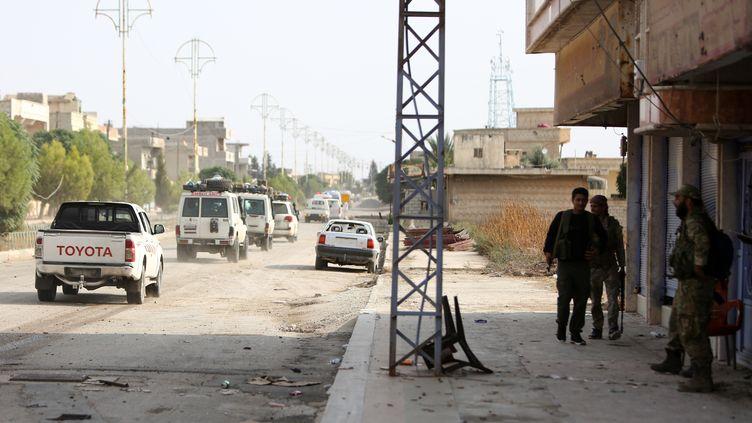Des soldats syriens soutenus par la Turquie surveillent des ambulances évacuant des combattants kurdes des Forces démocratiques syriennes (FDS), ainsi que des civils blessés, le 20 octobre 2019 à Ras al-Aïn (Syrie). (NAZEER AL-KHATIB / AFP)