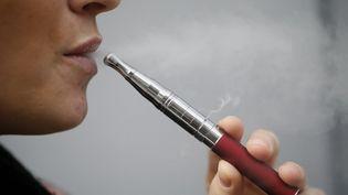 Une femme avec sa cigarette électronique à Paris, le 5 mars 2013.Près de 500 000 Français l'auraient désormais adoptée. (KENZO TRIBOUILLARD / AFP)
