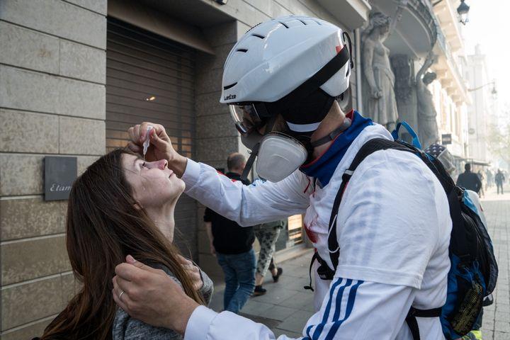 """Un """"street medic"""" met du sérumphysiologique dans les yeux d'une femme, lors d'une manifestation des """"gilets jaunes"""", le 23 mars 2019 à Lyon. (NICOLAS LIPONNE / NURPHOTO / AFP)"""