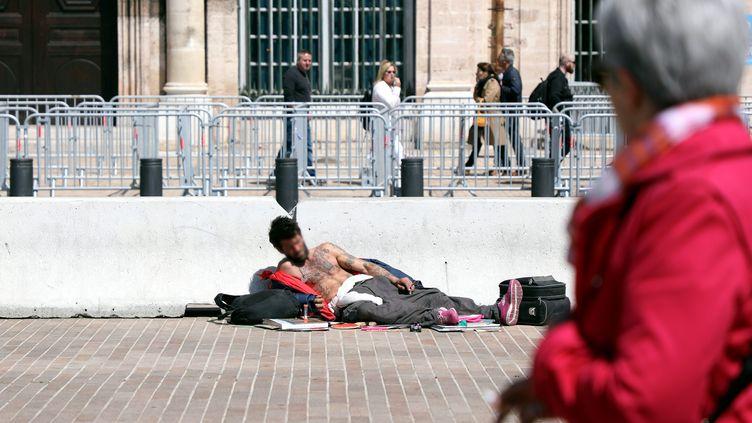 Un sans domicile fixe est allongé sur le sol dans une rue de Marseille, le 7 mai 2019. (NICOLAS VALLAURI / MAXPPP)