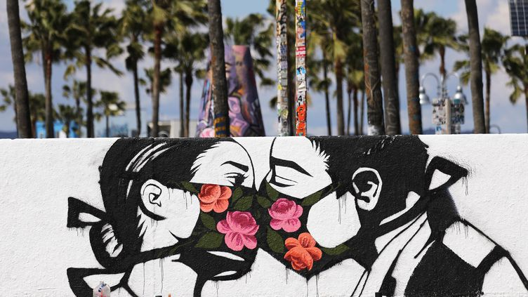 L'artiste Pony Wave a peint ces amoureux au temps du coronavirus sur un mur de Venice Beach, en Californie (Etats-Unis) avant le confinement décrété par le gouverneur de l'Etat Gavin Newsom pour faire face à la pandemie de Covid-19. (MARIO TAMA / GETTY IMAGES NORTH AMERICA)