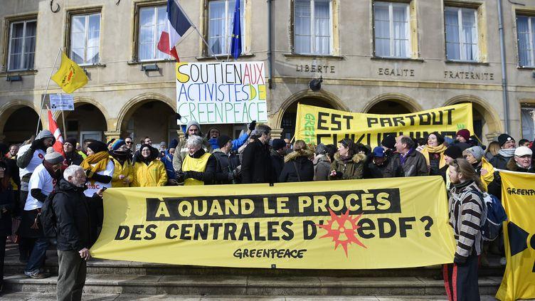Les activistes de Greenpeace manifestent devant la mairie de Thionville, le 27 février 2018, lors d'un procès de huit militants et deux dirigeants de Greenpeace France pour une action menée à l'intérieur de la centrale nucléaire de Cattenom en octobre 2017. (JEAN-CHRISTOPHE VERHAEGEN / AFP)