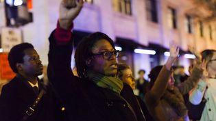 A Washington, une jeune femme au poing levé pour protester contre la non poursuite de l'officier blanc impliqué dans la mort d'Eric Garner. Le geste est celui des Black Panthers et des athlètes noirs américains Tommie Smith et John Carlos, médailles d'or et de bronze en 1968 aux Jeux Olympiques de Mexico, dénonçant la ségrégation raciale aux Etats-Unis. (SAMUEL CORUM / ANADOLU AGENCY / AFP)