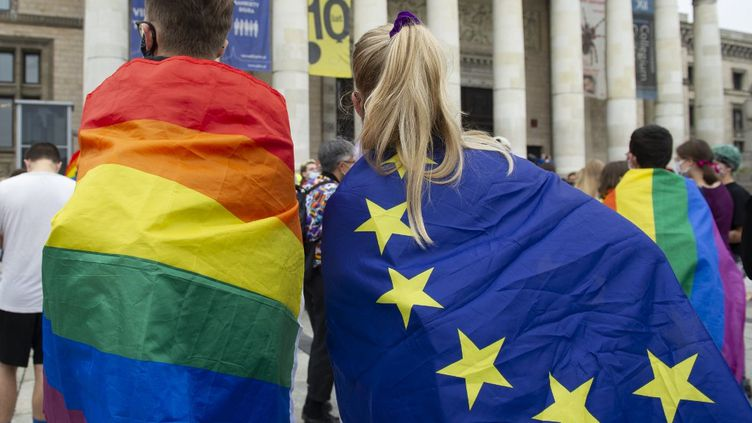 Des manifestants enveloppés dans des drapeaux LGBT et de l'Union européenne, le 30 août 2020 à Varsovie, en Pologne. (ALEKSANDER KALKA / NURPHOTO / NURPHOTO VIA AFP)