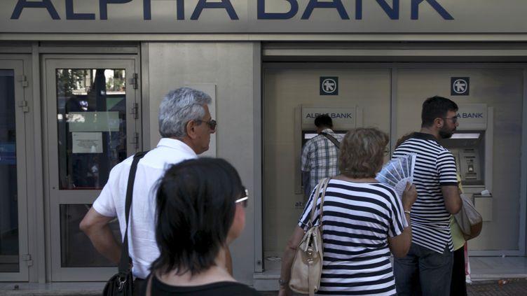 Des Grecs patientent avant de pouvoir retirer leur argent, à Athènes (Grèce), le 15 juillet 2015. (YIANNIS KOURTOGLOU / REUTERS)