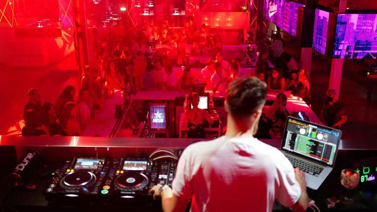 Un DJ joue dans une discothèque de La Grande Motte, le 10 juillet 2021. (SYLVAIN THOMAS / AFP)