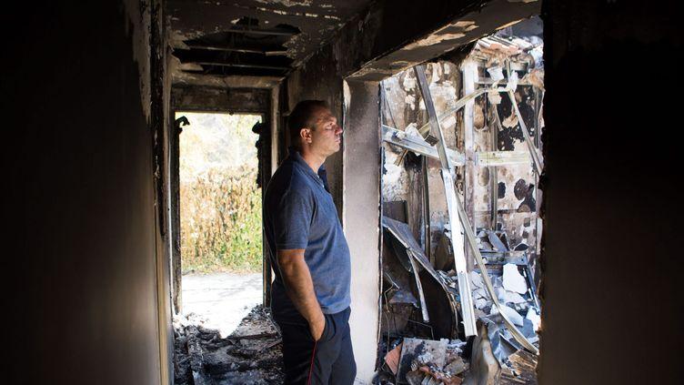 Un homme constate les dégâts des feux de forêt dans sa maison, aux Pennes-Mirabeau (Bouches-du-Rhône), le 11 août 2016. (MAXPPP)
