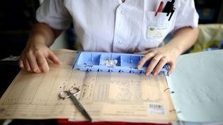 Une infirmière prépare le pilulier d'un patient à l'hopital d'Angers (Maine-et-Loire). (JEAN-SEBASTIEN EVRARD / AFP)