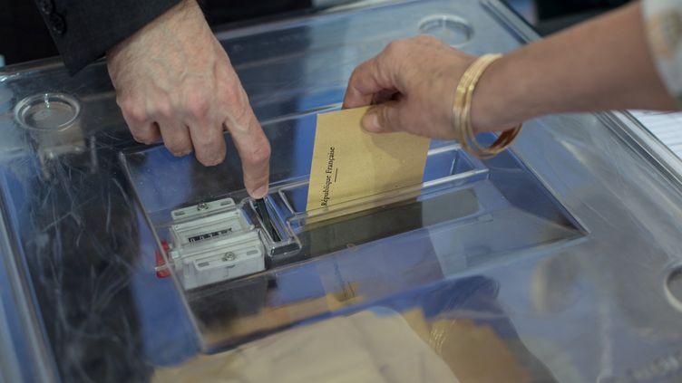 Une électrice glisse un bulletin de vote dans l'urne, dimanche 23 avril 2017 dans un bureau de vote de Bordeaux (Gironde). (CONSTANT FORME-BECHERAT / HANS LUCAS / AFP)